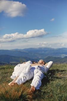 Älterer mann und frau in den bergen. erwachsenes paar verliebt in sonnenuntergang. mann in einem weißen hemd. leute, die auf einem himmelhintergrund liegen.