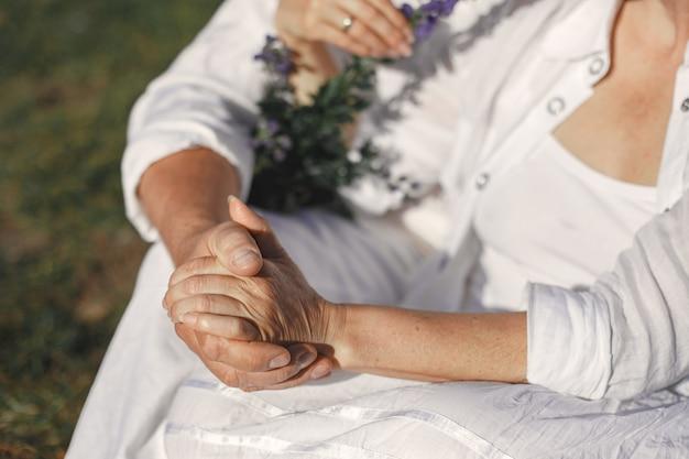 Älterer mann und frau in den bergen. erwachsenes paar verliebt in sonnenuntergang. mann in einem weißen hemd.