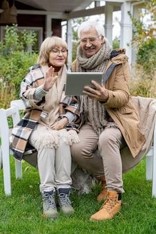 Älterer mann und frau mit digitalem tablet kommunizieren im video-chat, während sie auf einer bank auf grünem rasen vor ihrem landhaus sitzen