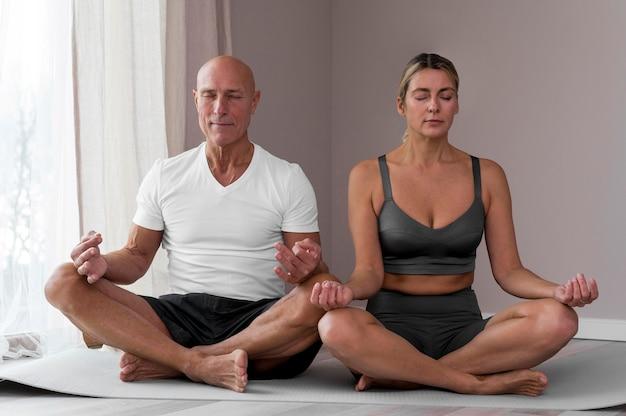 Älterer mann und frau sitzen in lotussitz