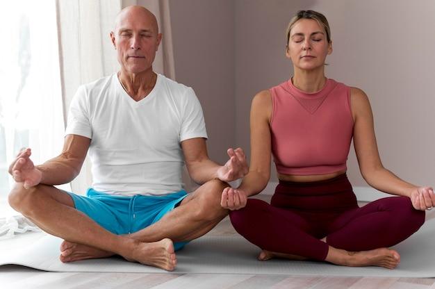 Älterer mann und frau sitzen in yoga-position