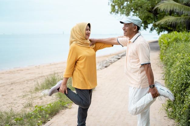 Älterer mann und frau unterstützen sich gegenseitig beim dehnen