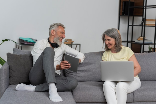 Älterer mann und frau zu hause auf der couch mit laptop und tablet