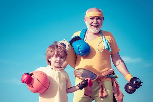Älterer mann und kind, die auf blauem himmel trainieren. sportübung für kinder. porträt eines gesunden vaters