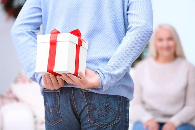 Älterer mann versteckt weihnachtsgeschenk für seine frau zu hause
