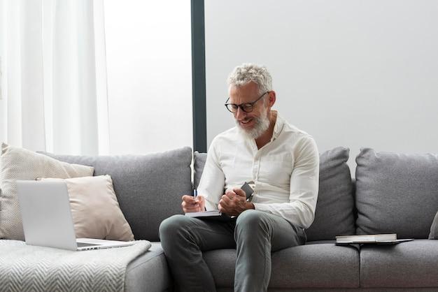 Älterer mann zu hause, der am laptop lernt und notizen macht Kostenlose Fotos