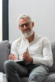 Älterer mann zu hause lernt und macht sich notizen