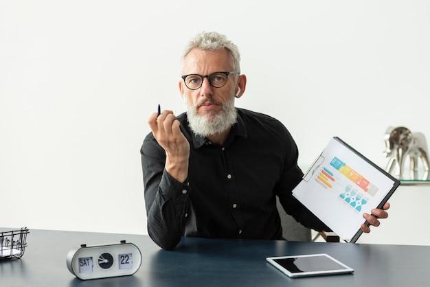 Älterer mann zu hause mit grafik auf notizblock mit tablet auf dem schreibtisch