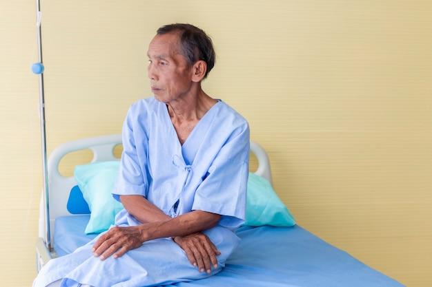 Älterer mannpatient, der in einem krankenhausbett denkt
