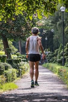 Älterer mannrüttler sein rüttelnder lauf auf straßenläufer in einem park im freien für die übung gesund