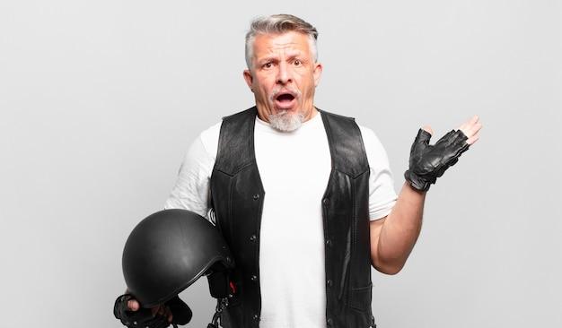 Älterer motorradfahrer, der überrascht und schockiert aussieht, mit heruntergefallenem kiefer, der ein objekt mit einer offenen hand an der seite hält