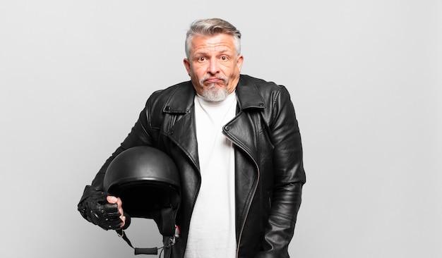 Älterer motorradfahrer zuckt mit den schultern, fühlt sich verwirrt und unsicher, zweifelt mit verschränkten armen und verwirrtem blick