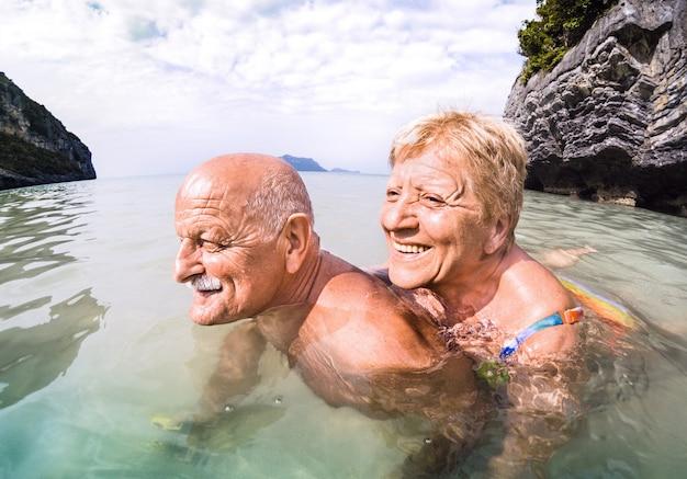 Älterer paarurlauber, der echten spielerischen spaß auf tropischem strand in thailand hat