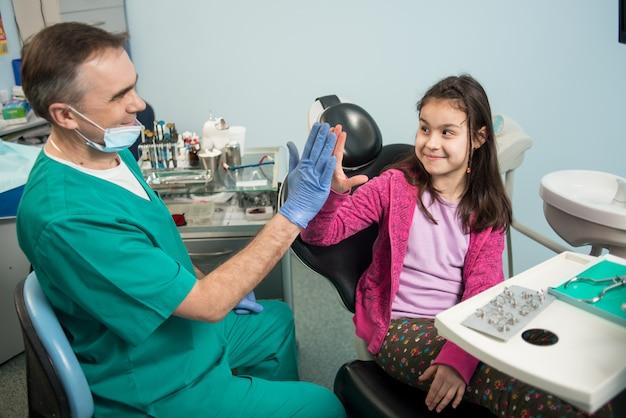 Älterer pädiatrischer zahnarzt und reizendes kind, nachdem zähne im zahnmedizinischen klinikbüro behandelt worden sind, high-five gelächelt und gegeben worden sind