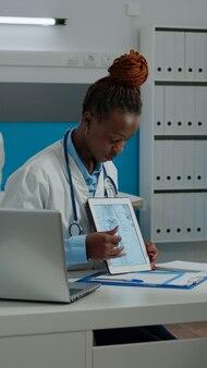 Älterer patient, der die illustration des skeletts auf dem tablet betrachtet