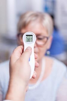 Älterer patient mit hoher temperatur, die während der ärztlichen untersuchung mit einem infrarot-thermometer gemessen wurde