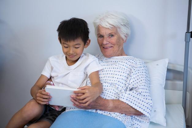 Älterer patient und junge, die digitales tablett halten