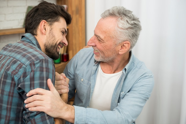 Älterer positiver mann und junger glücklicher kerl mit den händen umklammert im raum