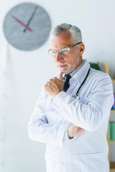 Älterer praktizierender arzt, der im büro denkt