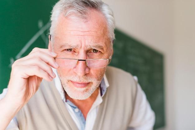 Älterer professor, der auf gläser in klassenzimmer sich setzt