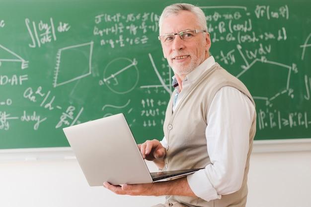 Älterer professor, der auf laptop im klassenzimmer schreibt
