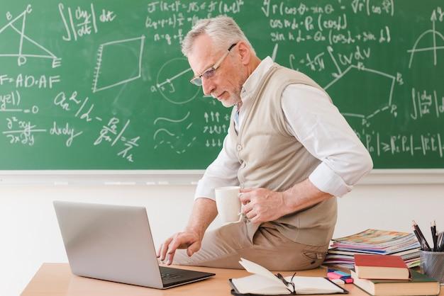 Älterer professor, der auf schreibtisch sitzt und auf laptop schreibt