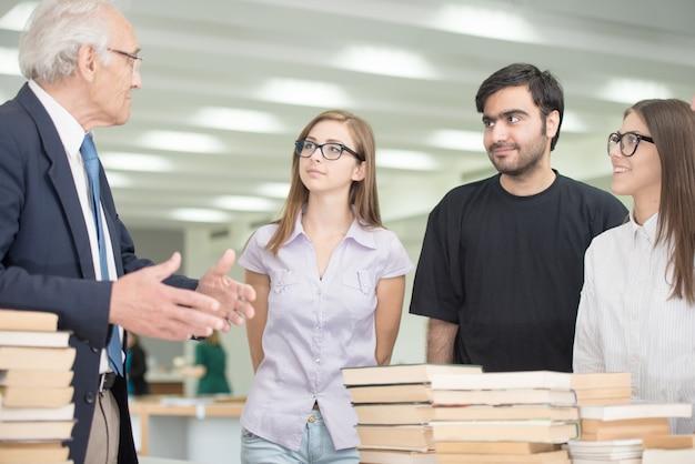 Älterer professor, der den jungen studenten auf hochschulcampus vortrag gibt
