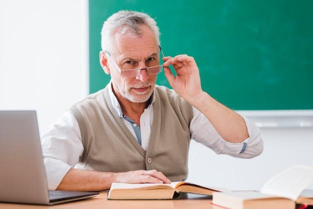Älterer professor, der gläser korrigiert und kamera im klassenzimmer betrachtet