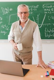 Älterer professor, der hinter schreibtisch im klassenzimmer steht