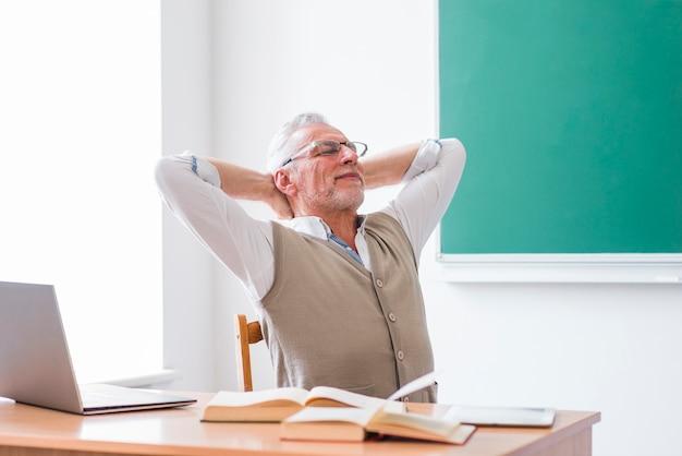 Älterer professor, der im klassenzimmer mit den händen hinter kopf sitzt