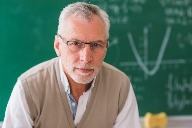 Älterer professor, der kamera gegen tafel mit mathebeispiel betrachtet