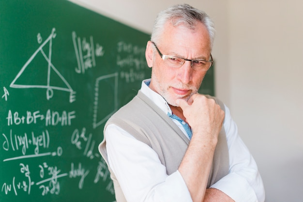 Älterer professor, der nahe tafel im hörsaal steht