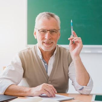Älterer professor mit angehobenem handbehälter im klassenzimmer