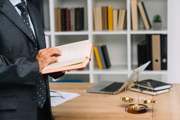 Älterer rechtsanwalt, der gesetzbuch im gerichtssaal liest