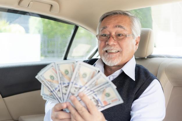 Älterer reicher mann des geschäfts, der in der hand geld us-dollar rechnungen auf seinem autohintergrund hält