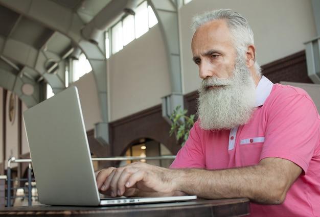 Älterer reifer geschäftsmann, der einen kaffee in einem coffeeshop hat und an seinem laptop arbeitet