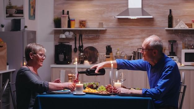 Älterer reifer mann, der seiner frau beim romantischen abendessen rotwein serviert. älteres paar sitzt am tisch in der küche, redet, genießt das essen, feiert ihr jubiläum im esszimmer.