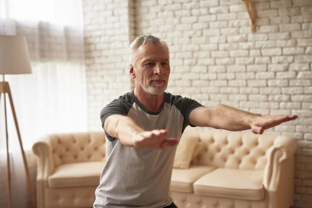 Älterer reifer sportler, der vorwärts hände ausdehnt.