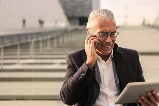 Älterer reizend geschäftsmann, der auf einem smartphone spricht