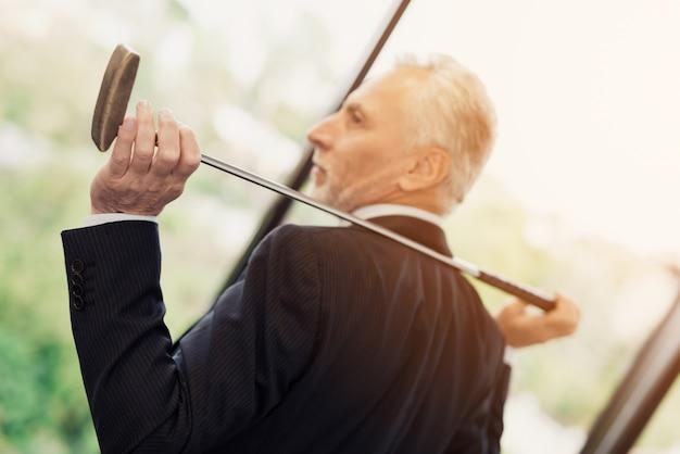 Älterer respektabler mann, der im büro mit einem golfclub aufwirft. Premium Fotos