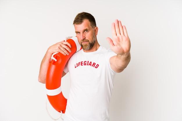 Älterer rettungsschwimmermann isoliert auf weißem stehen mit ausgestreckter hand, die stoppschild zeigt und sie verhindert.