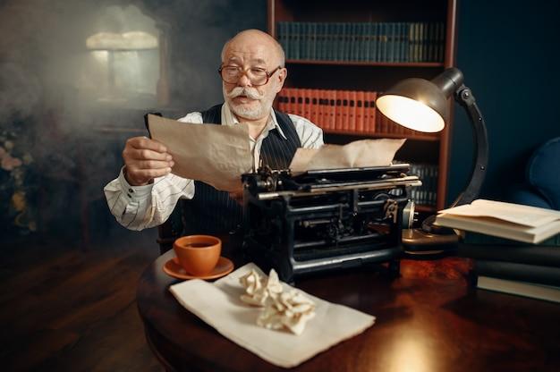 Älterer schriftsteller arbeitet in seinem heimbüro an einer alten schreibmaschine. alter mann mit brille schreibt literaturroman im zimmer mit rauch
