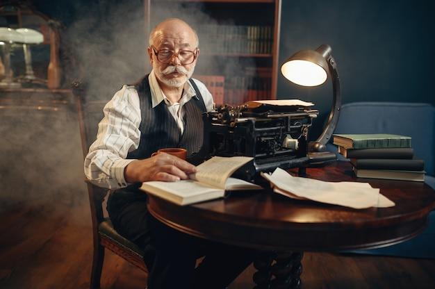 Älterer schriftsteller arbeitet in seinem heimbüro an einer alten schreibmaschine. alter mann mit brille schreibt literaturroman