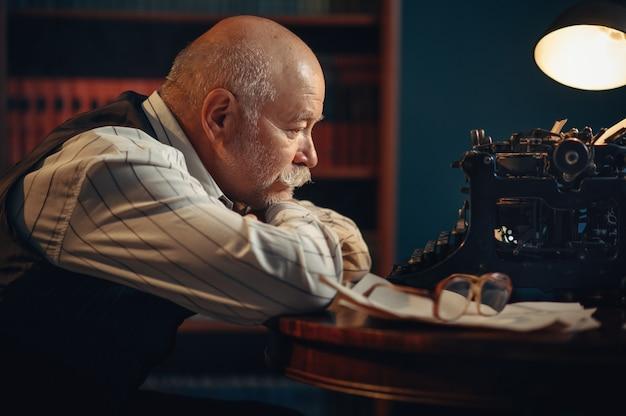 Älterer schriftsteller denkt an vintage-schreibmaschine im home office. alter mann mit brille schreibt literaturroman im zimmer mit rauch, inspiration