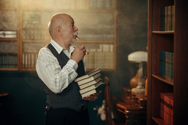 Älterer schriftsteller hält stapel bücher im home office. alter mann mit brille schreibt literaturroman im zimmer mit rauch, inspiration