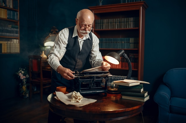 Älterer schriftsteller legt papier in die schreibmaschine ein