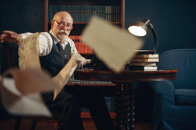 Älterer schriftsteller wirft papierbögen im homeoffice. alter mann mit brille schreibt literaturroman im zimmer mit rauch, inspiration
