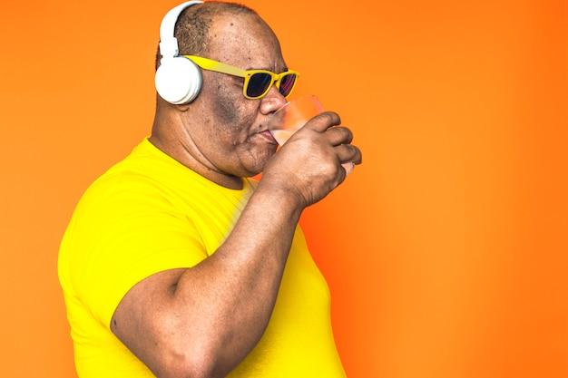 Älterer schwarzer mann, der ein glas kaltes wasser trinkt und musik auf seinen kopfhörern und mit sonnenbrille auf seinem gesicht hört.