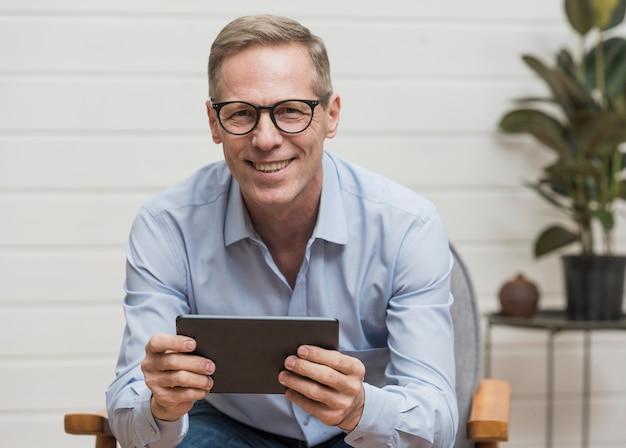 Älterer smileymann, der seine tablette hält