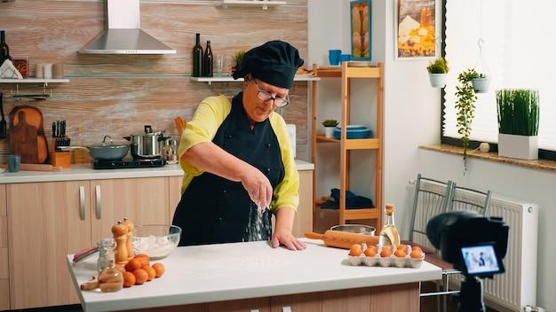 Älterer social-media-influencer kocht brot mit kamera auf stativ in der küche. blogger-koch im ruhestand, der internet-technologie verwendet, kommuniziert und blogging mit digitaler ausrüstung fotografiert
